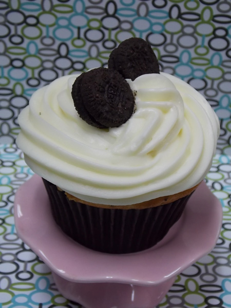 Vanilla cupcake with Oreo cookie chunks baked in and topped  with white chocolate cream cheese and mini Oreo cookies