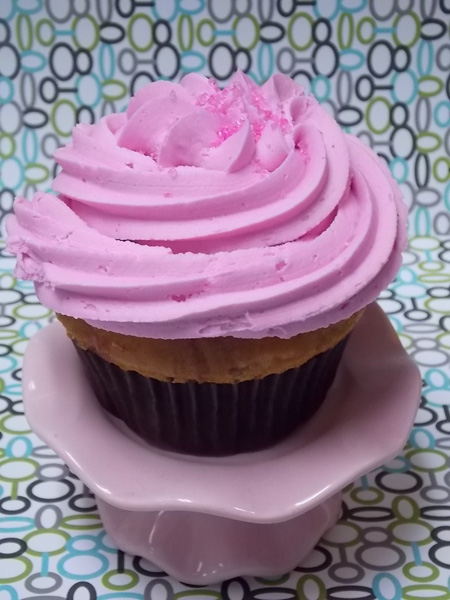 Vanilla cupcake with a ribbon of raspberry throughout and topped with raspberry buttercream.