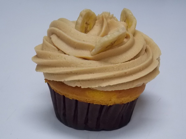 Banana cupcake with peanut butter cream icing and a few candied banana chips