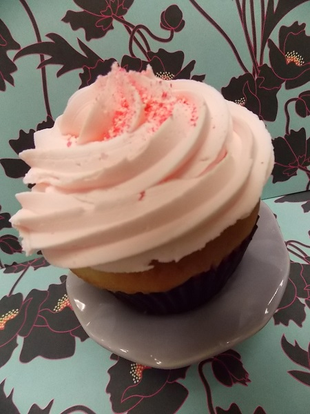 Cherry Cheesecake-Vanilla cupcake filled with cream cheese and topped with Washington Cherry buttercream and a sprinkling of cherry bark
