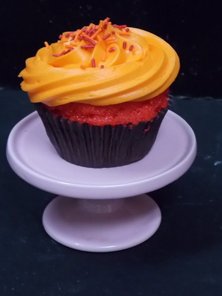 The POMinator-A tart pomegranate cupcake topped with a sweet tangerine cream cheese icing